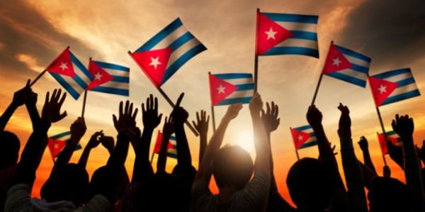 Siluetas de personas que tienen la bandera de Cuba