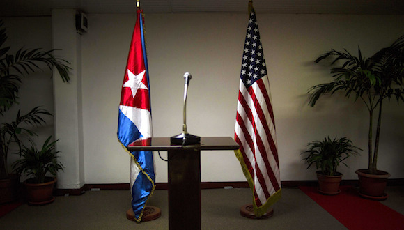 A Cuban flag and an American flag stand in the press room during the second day of talks between U.S. and Cuban officials, in Havana, Cuba, Thursday, Jan. 22, 2015. The United States and Cuba are trying to eliminate obstacles to normalized ties as the highest-level U.S. delegation to the communist island in more than three decades holds a second day of talks with Cuban officials. (AP Photo/Ramon Espinosa)